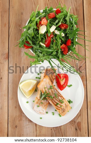 healthy sea food : roasted pink salmon fillet with vegetable salad on white dish over wooden table