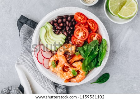 Healthy seafood lunch. Spicy Shrimp Burrito Buddha Bowl with wild rice, spinach, radish,  tomatoes, black beans and avocado