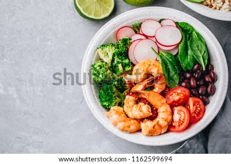 Healthy seafood lunch. Spicy Shrimp Burrito Buddha Bowl with wild rice, spinach, radish,  tomatoes, black beans and broccoli