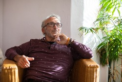 Healthy senior man living with HIV sitting in a whicker chair and thinking