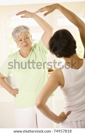 Healthy senior woman doing exercises with personal trainer at home, smiling.?