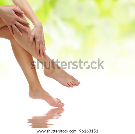 healthy sexy slender female legs being massaged over green natural spring background - spa and healthcare concept