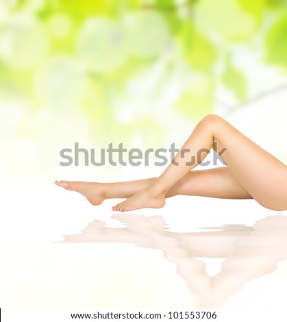 healthy sexy slender female legs on water waves over green natural spring background - spa and healthcare concept