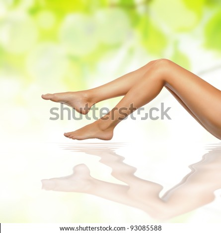 healthy sexy slender female legs over green natural spring background - spa and healthcare concept