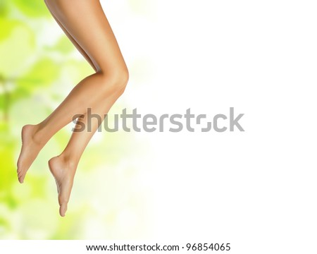healthy sexy slender female legs over green natural spring background with white copyspace - spa and healthcare concept