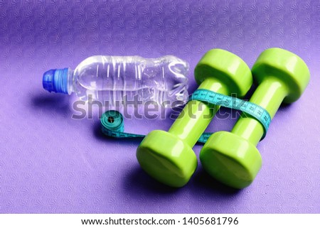 Healthy shape and sport concept. Barbells next to roll of tape measure and water bottle. Shaping and fitness equipment. Dumbbells and measure tape in cyan blue color on purple background #1405681796