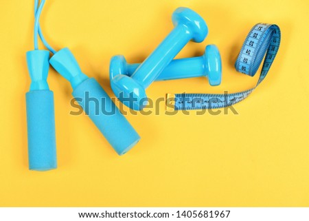 Healthy shape and sport concept. Dumbbells and jump rope in cyan color isolated on yellow background. Shaping and fitness equipment. Barbells and skipping rope next to measure tape roll, top view #1405681967