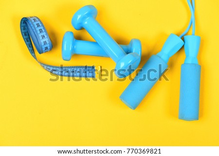 Healthy shape and sport concept. Dumbbells and jump rope in cyan color isolated on yellow background. Shaping and fitness equipment. Barbells and skipping rope next to measure tape roll, top view #770369821