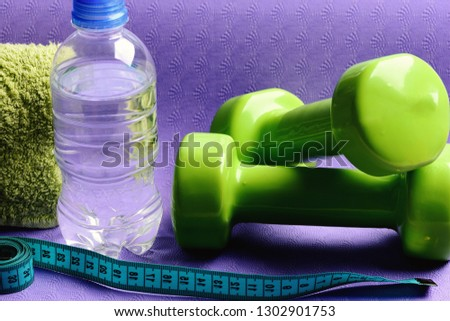 Healthy shape and sport concept. Dumbbells made of green plastic on purple background, close up. Shaping and fitness equipment. Barbells near water bottle and soft towel lying on yoga mat #1302901753