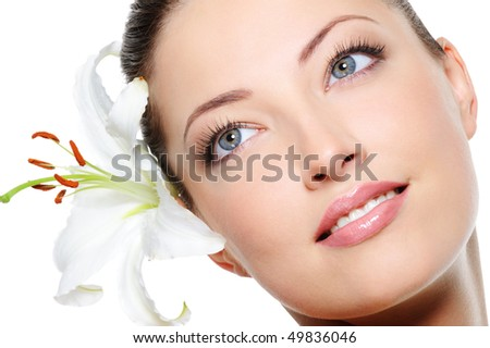 Healthy skin of young beautiful woman face with a flower in her hairs - stock photo