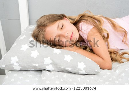 Healthy sleep tips. Girl sleep on little pillow bedclothes background. Kid long curly hair fall asleep pillow close up. Choose proper pillow to relax. Cute pillow and bedclothes for childish bedroom.