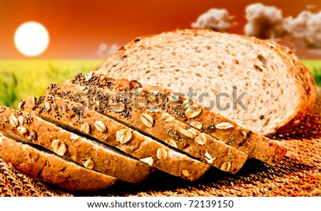 Healthy sliced whole wheat bread with the sun going down over a green wheat field