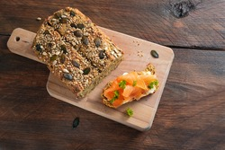 Healthy slimming with low carb or ketogenic diet, protein bread and sandwich with salmon and herb garnish on a cutting board and on a dark rustic wooden table, copy space, high angle view from above
