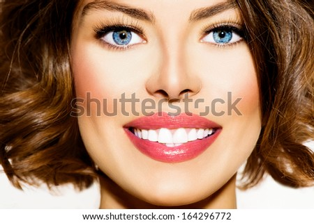 Healthy Smile. Teeth Whitening. Beautiful Smiling Young Woman Portrait close up. Over White background . Laughing Girl with Perfect Shin
