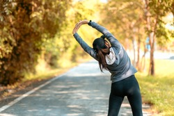 Healthy smiling woman warming up stretching her arms and looking away in the road outdoor. Asian runner woman workout before fitness and jogging session workout in park. Healthy and Lifestyle Concept.