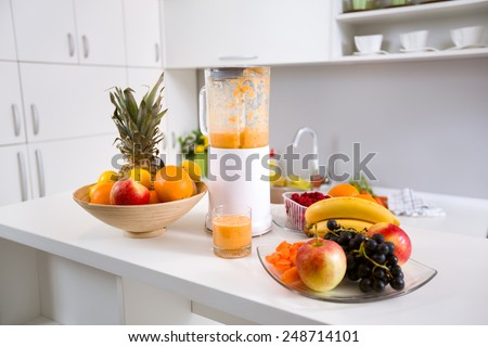 healthy smoothie ingredients in blender with fresh fruit on kitchen table