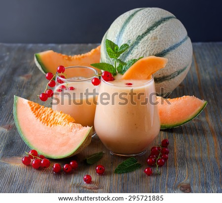 Healthy smoothie vitamins drink with red currant fresh berries, mint and cantaloupe melon, shake with yogurt for breakfast on wooden rustic background, summer harvest beverage, diet concept