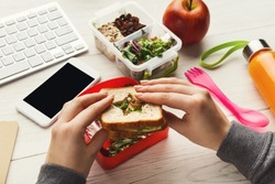 Healthy snack at office workplace. Businesswoman eating organic vegan meals from take away lunch box at wooden working table with computer keyboard and smartphone