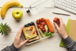 Healthy snack at office workplace. Businesswoman eating organic vegan meals from take away lunch box at wooden working table with computer keyboard, top view