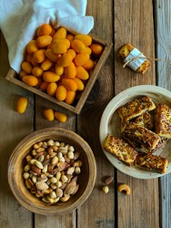Healthy snack cumquat , nuts and dates arabic sweets on wooden background