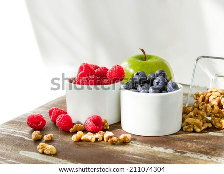 Healthy snack foods with raspberries, blueberries, green apple and walnuts