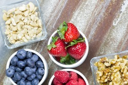 Healthy snack foods with small bowls of raspberries, blueberries, strawberries, cashews and walnuts