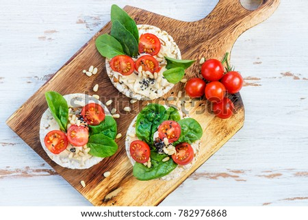 Healthy Snack from Rice Cakes with Hummus, Spinach and Tomatoes on Light Wooden Background
