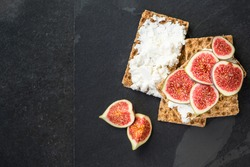 Healthy snack from wholegrain rye crispbread crackers, figs and ricotta cheese on dark slate board