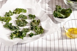 Healthy snack kale chips with salt and seasoning on a baking paper.Low-carb and gluten free vegetable crisps snack.Horizontal orientation