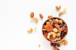 healthy snack: mixed nuts and dried fruits in wooden bowl on white background, almond, pineapple, cranberry, papaya, apple, strawberry, cherry, apricot, cashew.