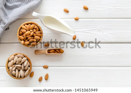 Healthy snack with almonds for milk on white wooden background top view mock up #1451065949