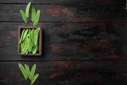 Healthy snap peas set, in wooden box, on old dark wooden table background, top view flat lay , with copyspace and space for text