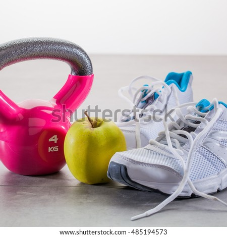 healthy sport lifestyle concept - close up of pink kettle bell with sneakers and a healthy apple over gym floor #485194573