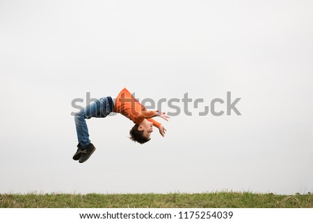healthy sport little caucasian boy jumping somersault outdoors nature with copyspace #1175254039