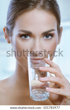 Healthy sport woman drinks cold water from glass