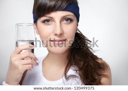 Healthy sport woman holds a glass with water