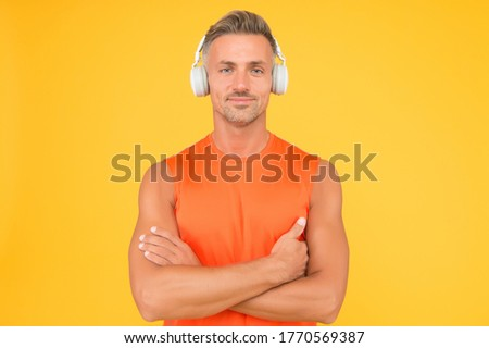 Healthy sportsman or athlete. Sport and fitness. Music for fitness. Sportsman listen music. Sportsman training. Regular workout. Mature coach. Strong sportsman wear headphones and fitness uniform.