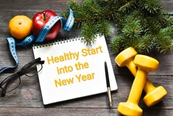 HEALTHY START INTO THE NEW YEAR. Text written in notepad with measuring tape, orange, apple, dumbbells and fir branches on a wooden background. Fitness motivation, concepts sport, healthy. Sport chris