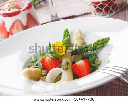 Healthy strawberry and asparagus salad with succulent green and white asparagus tips and sliced ripe red strawberries served in a white dish