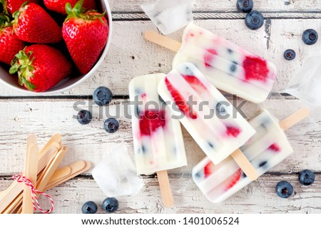 Healthy strawberry blueberry yogurt popsicles, top view summer table scene against a white wood background