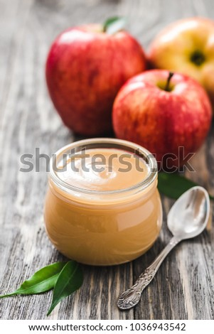 Healthy sugar free applesauce in glass jar and red ripe apples on rustic wooden background. Selective focus, space for text.  stock photo