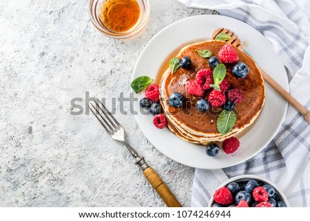 Photo of  Healthy summer breakfast,homemade classic american pancakes with fresh berry and honey, morning light grey stone background copy space top view