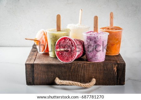 Healthy summer desserts. Ice cream popsicles. Frozen tropical juices, smoothies blueberries. currants, orange, mango, kiwi, banana, coconut, raspberry. On white marble table,wooden  tray copy space