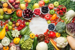 Healthy summer fruits vegetables berries arranged in a circle frame, cherries peaches strawberries cabbage broccoli cauliflower squash tomatoes carrots beetroot, copy space, top view, selective focus