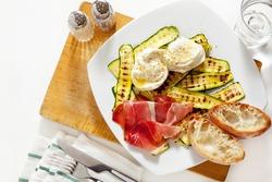 healthy summer salad with grilled zucchini, mozzarella and prosciutto. Fresh sliced bread ciabatta. On white.