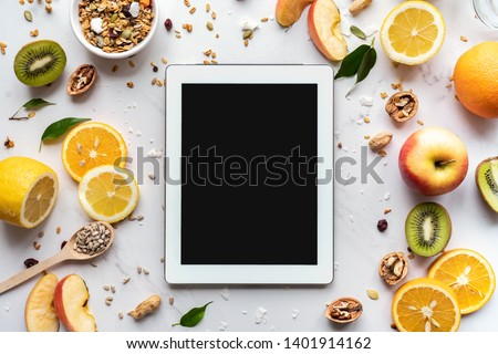 Healthy super food and technology background, digital tablet computer apps for cooking diet nutrition plan, fresh fruit granola seeds on white organic table, health care detox, top view mockup screen