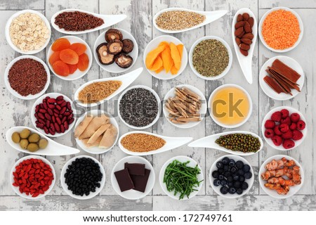 Healthy Super Food Selection In Porcelain Bowls Over Distressed Wooden Background.