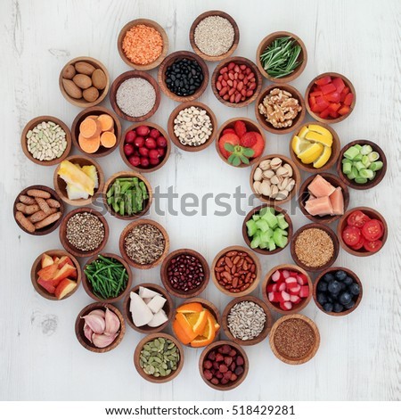Healthy super food selection in wooden bowls forming a wheel over distressed white wood background. High in antioxidants, vitamins, minerals and anthocyanins. Stock photo ©