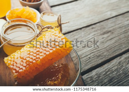 Healthy sweet. Different varieties of golden fresh honey and honeycombs on rustic wooden table, copy space #1175348716