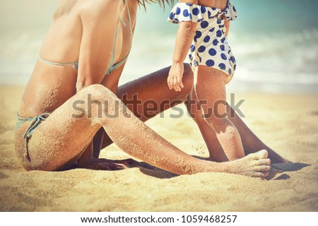 Healthy Tan Skin Woman on Soft Fluffy Sand Beach for Sunbath with Baby Girl Daughter.Happy Child Wearing a White Swimsuit Striped Blue Dot with Mother. #1059468257